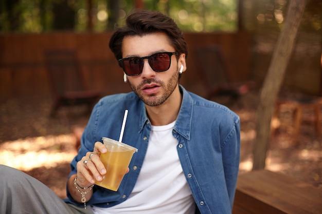 Mooie jonge bebaarde man die met ernstig gezicht kijkt, sap drinkt terwijl hij buiten op openbare plaats zit, vrijetijdskleding draagt