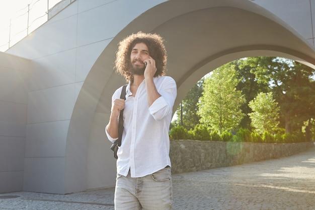 Mooie jonge bebaarde man met bruin krullend haar wandelen in het groene stadspark op zonnige warme dag, vrolijk kijken tijdens het bellen met zijn mobiele telefoon