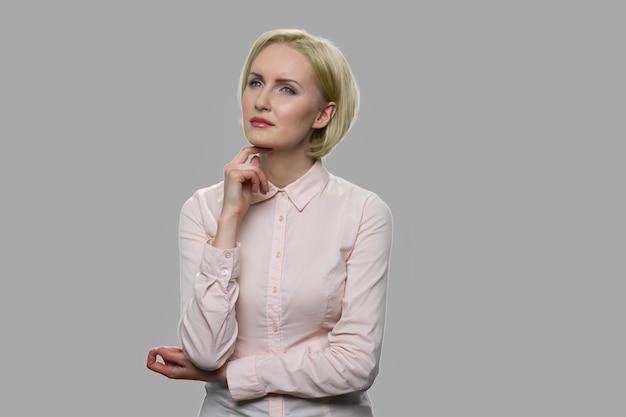 Mooie jonge bedrijfsvrouw met peinzende uitdrukking. elegante peinzende zakelijke dame met hand onder de kin op een grijze achtergrond.