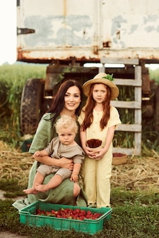 Mooie jonge blanke moeder met haar kinderen in een linnen jurk met een mandje aardbeien verzamelt een nieuwe oogst en heeft plezier met de kinderen bij de trailer