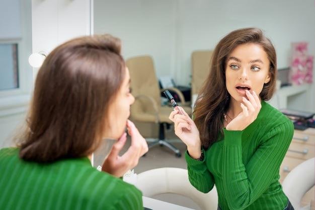 Mooie jonge blanke vrouw glans toe te passen op de lippen door vinger in de spiegel kijken