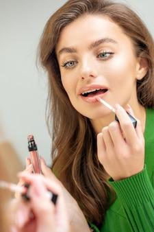 Mooie jonge blanke vrouw glans toe te passen op de lippen in de spiegel kijken