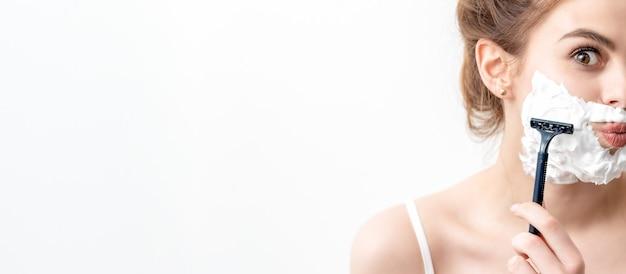 Mooie jonge blanke vrouw haar gezicht scheren door scheermes. mooie vrouw met scheerschuim op haar gezicht