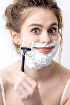 Mooie jonge blanke vrouw haar gezicht scheren door scheermes op witte achtergrond. mooie vrouw met scheerschuim op haar gezicht