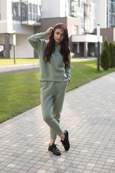 Mooie jonge blanke vrouw in groen sportpak en zwarte sneakers gaat wandelen naar de stad