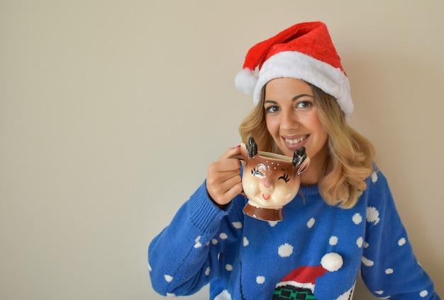 Mooie jonge blanke vrouw in schattige blauwe kerst outfit en kerstmuts warme chocolademelk drinken