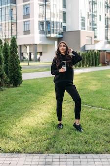 Mooie jonge blanke vrouw in zwart sportpak en zwarte sneakers gaat wandelen naar de stad met een kopje koffie