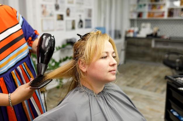 Mooie jonge blanke vrouw met blond lang haar kijkt in een spiegel in een schoonheidssalon