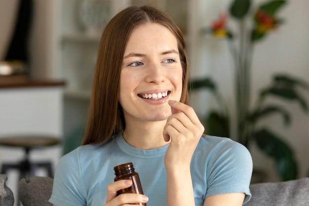 Mooie jonge blanke vrouw met glas water drinkt vitamines thuis. gezond levensstijlconcept, glimlachend