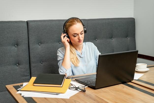 Mooie jonge blanke vrouw met koptelefoon en laptop zitten aan de tafel in een café