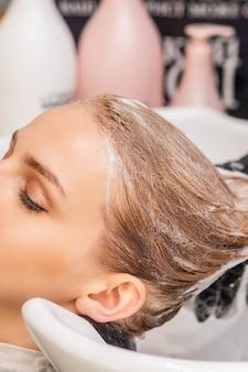 Mooie jonge blanke vrouw wassen haar haren in een kapsalon ontvangen