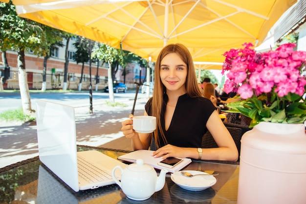 Mooie jonge blanke vrouw zit aan een tafel met een laptop in een café, drinkt thee en glimlacht. het concept van werken op afstand, freelancen en online leren op afstand