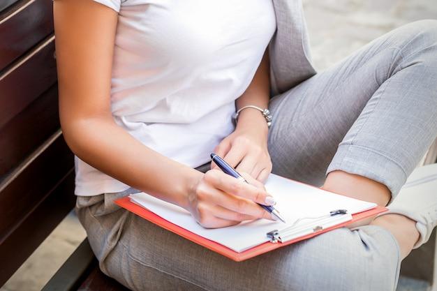 Mooie jonge blanke vrouw zit op de bank met smartphone en blocnote over stadsstraat achtergrond