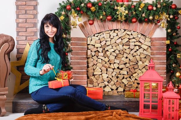 Mooie jonge blanke vrouw zitten in de buurt van een decoratieve open haard in een interieur van kerstmis.