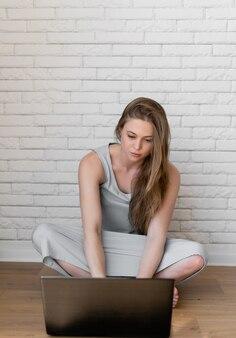 Mooie jonge blanke vrouw zittend op de vloer tijdens het typen op laptop op witte bakstenen achtergrond. communicatie, technologieconcept