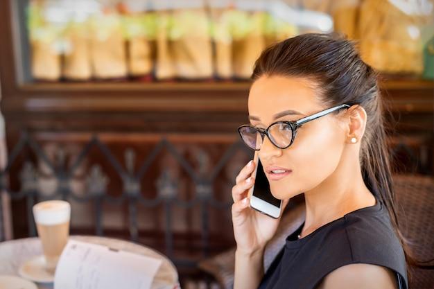 Mooie jonge blanke zakenvrouw met bril belt via de mobiele telefoon in café