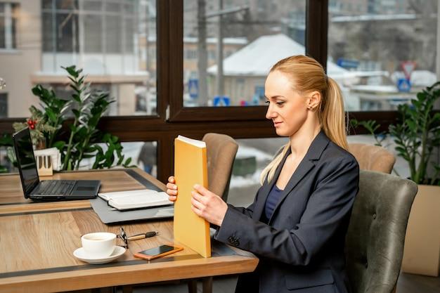 Mooie jonge blanke zakenvrouw met een map met documenten zitten aan de tafel in kantoor of café