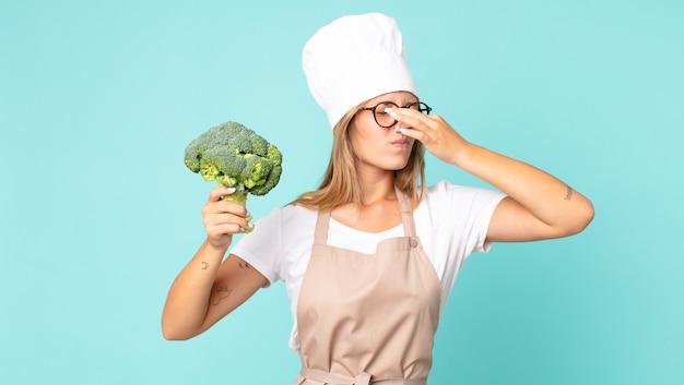 Mooie jonge blonde chef-kok vrouw met een broccoli