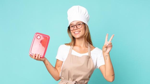 Mooie jonge blonde chef-kokvrouw en houdt een tupperware vast