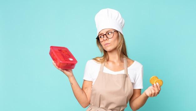 Mooie jonge blonde chef-kokvrouw en met een tupperware