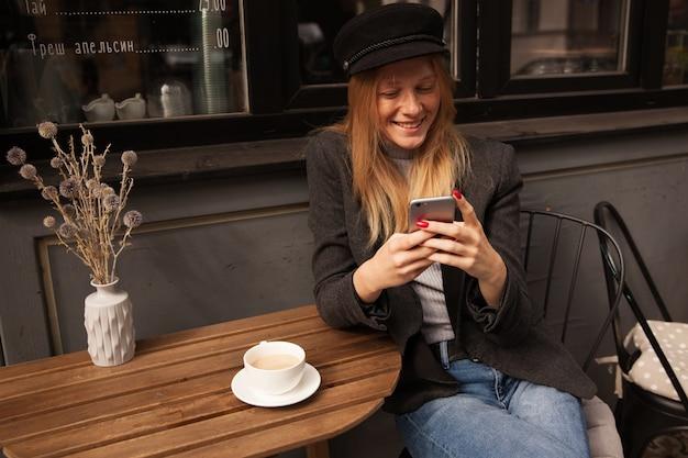 Mooie jonge blonde dame met een kopje koffie tijdens het wachten op haar vrienden in het stadscafé, vrolijk kijken naar het scherm tijdens het typen van bericht