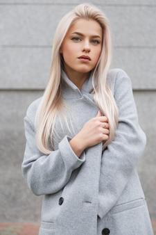 Mooie jonge blonde haren vrouw in grijze jas