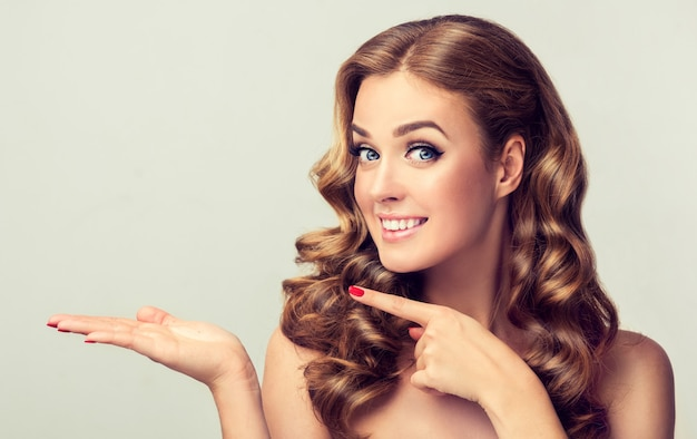 Mooie jonge blonde harige vrouw met brede glimlach op het gezicht demonstreert onzichtbaar product model met dicht krullend haar wijst met de vinger opzij bright veelzeggende gezichtsuitdrukking pin-up stijl