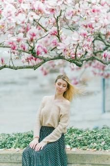 Mooie jonge blonde in de buurt van een bloeiende magnoliaboom