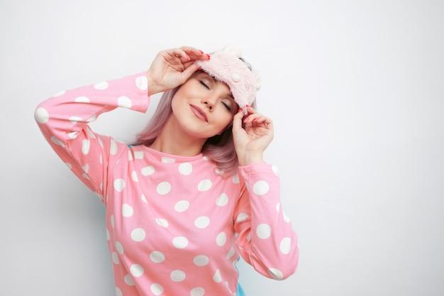 Mooie jonge blonde in roze pyjama en een slaapmasker