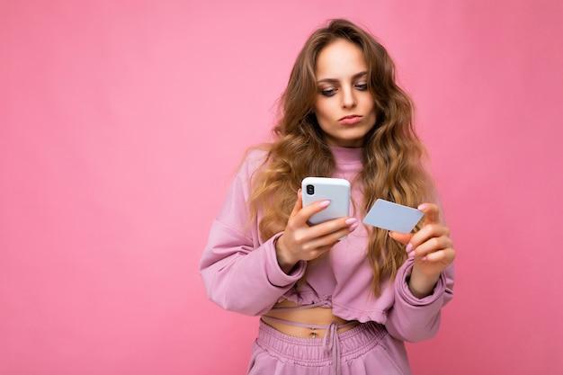 Mooie jonge blonde krullende vrouw die roze kleren draagt die over roze achtergrond wordt geïsoleerd die mobiel gebruiken