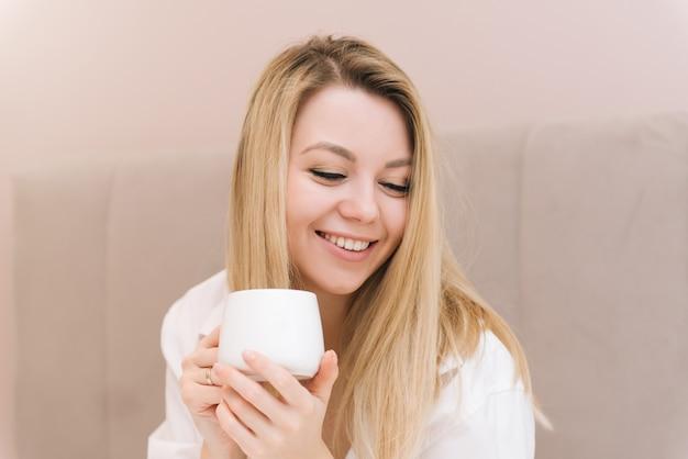Mooie jonge blonde lachende meisje met koffie in een wit bed, goedemorgen