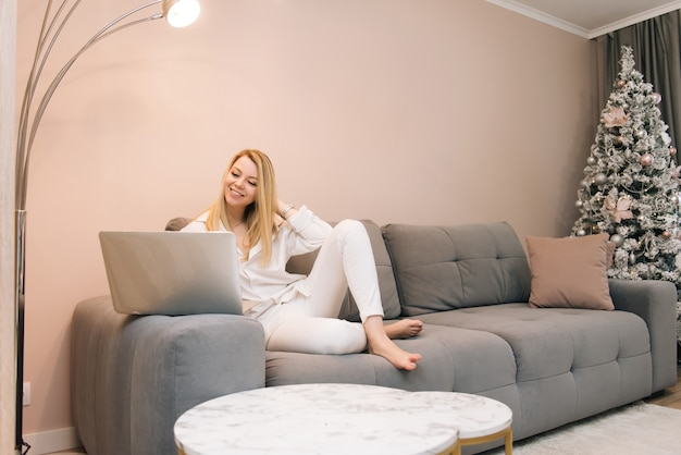 Mooie jonge blonde lachende meisje met laptop thuis op de bank, thuiswerken op afstand, isolatie