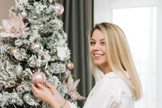 Mooie jonge blonde lachende meisje versiert het huis voor het nieuwe jaar