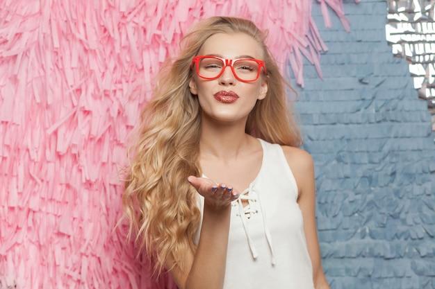 Mooie jonge blonde meid gekleed in witte top stuurt luchtkus naar camera