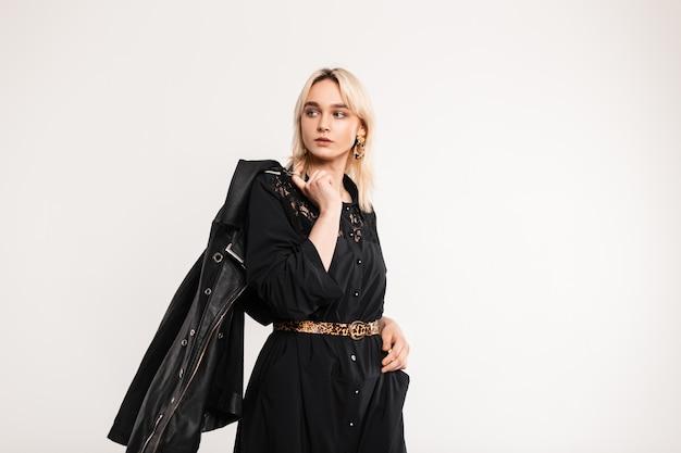 Mooie jonge blonde meid in een modieuze zwarte kanten jurk met een stijlvol leren jack