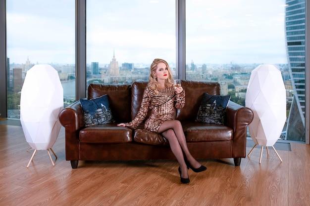 Mooie jonge blonde meisje in een modieuze jurk, die zich voordeed op een leren bank met een glas champagne tegen de achtergrond van een panoramisch raam met uitzicht op de wolkenkrabbers