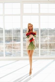 Mooie jonge blonde meisje vrouwelijke mannequin dragen korte jurk houden feestelijke rozen boeket poseren in de buurt van groot raam. hoge kwaliteit foto