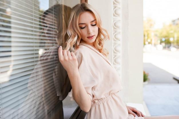 Mooie jonge blonde vrouw buiten. geniet van zonnige dag