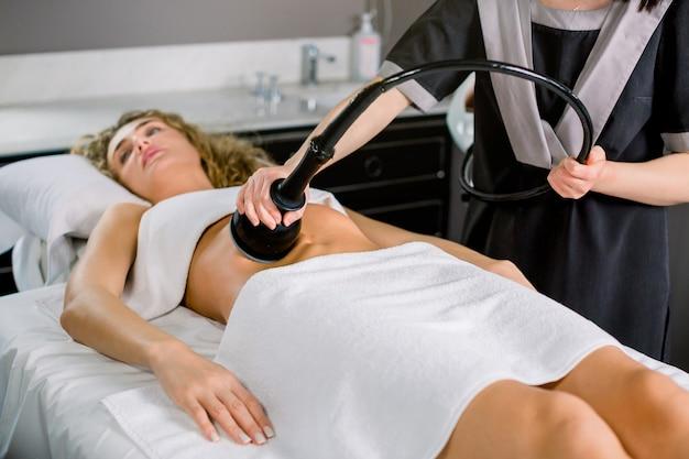 Mooie jonge blonde vrouw die anti-cellulite en anti-vette therapie op haar buik in schoonheidssalon krijgt.