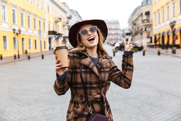 Mooie jonge blonde vrouw die een jas draagt die buiten loopt, afhaalmaaltijdenkoffie houdt