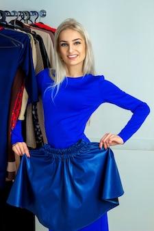 Mooie jonge blonde vrouw die een rok probeert