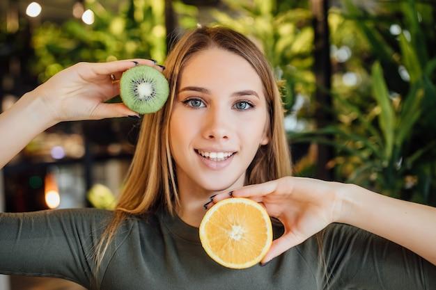 Mooie jonge blonde vrouw die een stuk avocado en kiwi voor haar oog houdt en haar gezicht aanraakt