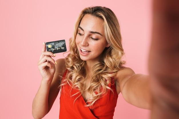 Mooie jonge blonde vrouw die een zomerjurk draagt die geïsoleerd over een roze muur staat, een selfie neemt en een plastic creditcard toont