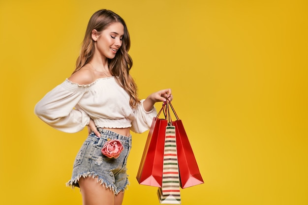 Mooie jonge blonde vrouw die lacht en boodschappentassen vasthoudt en naar hen kijkt op een gele muur.
