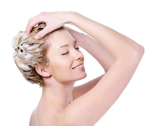 Mooie jonge blonde vrouw die met aantrekkelijke glimlach haar hoofd inzepen - dat op witte achtergrond wordt geïsoleerd