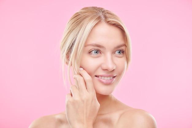 Mooie jonge blonde vrouw die met schoon en stralend gezicht met glimlach geïsoleerd over roze muur kijkt
