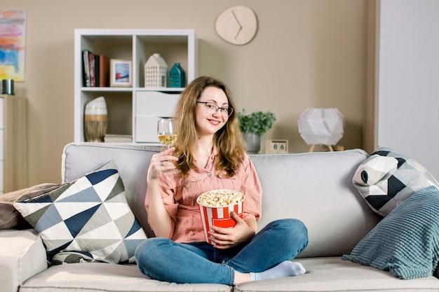 Mooie jonge blonde vrouw die op tv letten, wijn drinken en popcorn eten, terwijl thuis het zitten op grijze bank