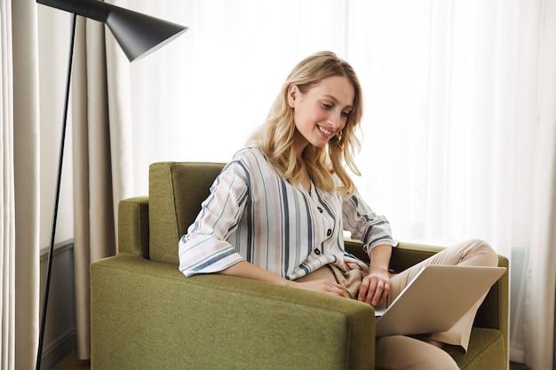 Mooie jonge blonde vrouw die thuis in een fauteuil zit en op een laptop werkt
