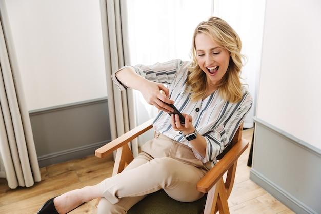 Mooie jonge blonde vrouw die thuis in een fauteuil zit, mobiele telefoon gebruikt, spelletjes speelt