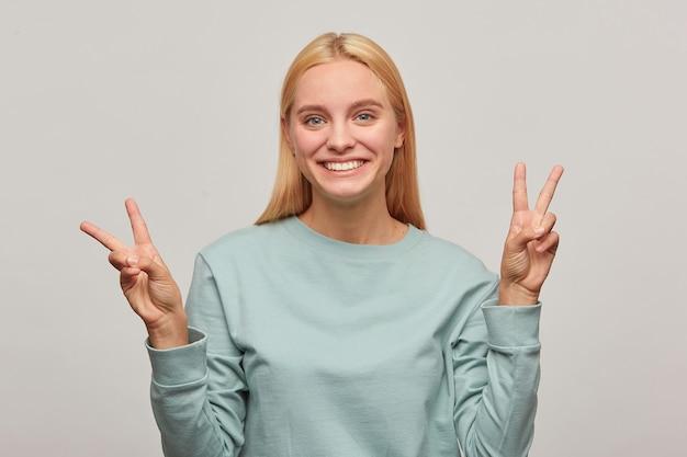 Mooie jonge blonde vrouw heeft plezier, glimlacht, toont overwinning vredesteken met vingers aan beide handen